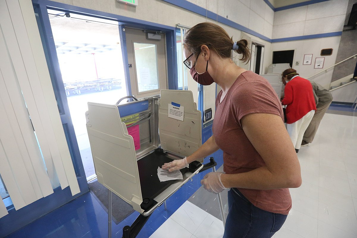 Poll worker sanitizes election booth
